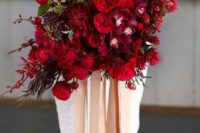 a deep red and fuchsia wedding bouquet with a catchy shape, some blooming branches and touches of foliage plus long ribbons