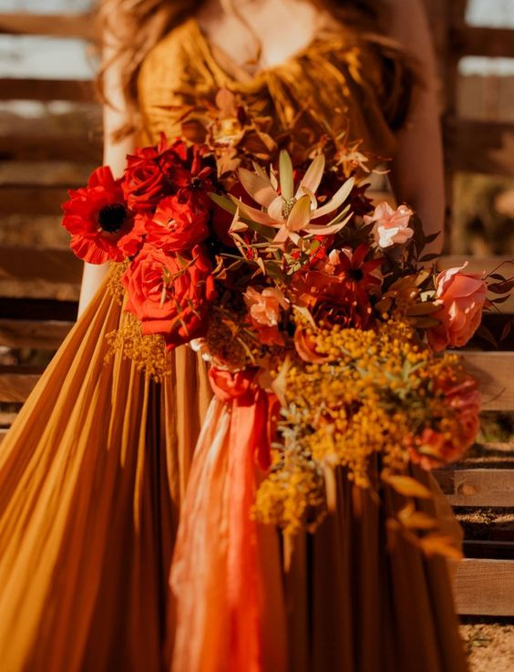 a deep red and rust wedding bouquet with fresh and dried blooms and herbs embraces the fall with its colors