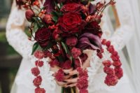 a deep red wedding bouquet with touches of purple and cascading elements okus blooming branches is elegant and decadent