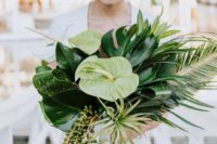 a green tropical wedding bouquet with succulents, air plants and large monstera leaves for a modern bride