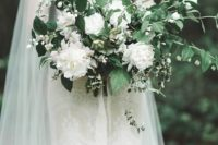 a romantic spring wedding bouquet of white blooms, blooming branches and some foliage
