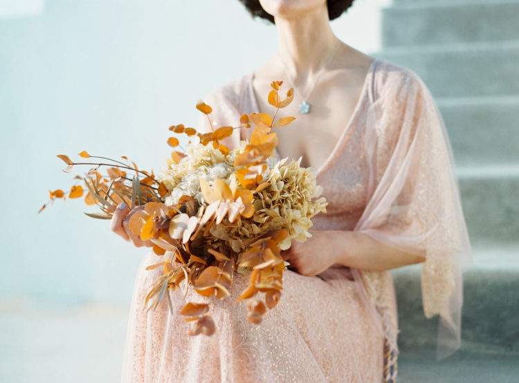 a rust-colored wedding buquet with dried eucalyptus and hydrangeas is a great idea for fall