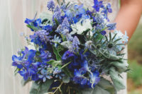 a statement blue wedding bouquet with a couple of white blooms and some greenery to make the flowers stand out