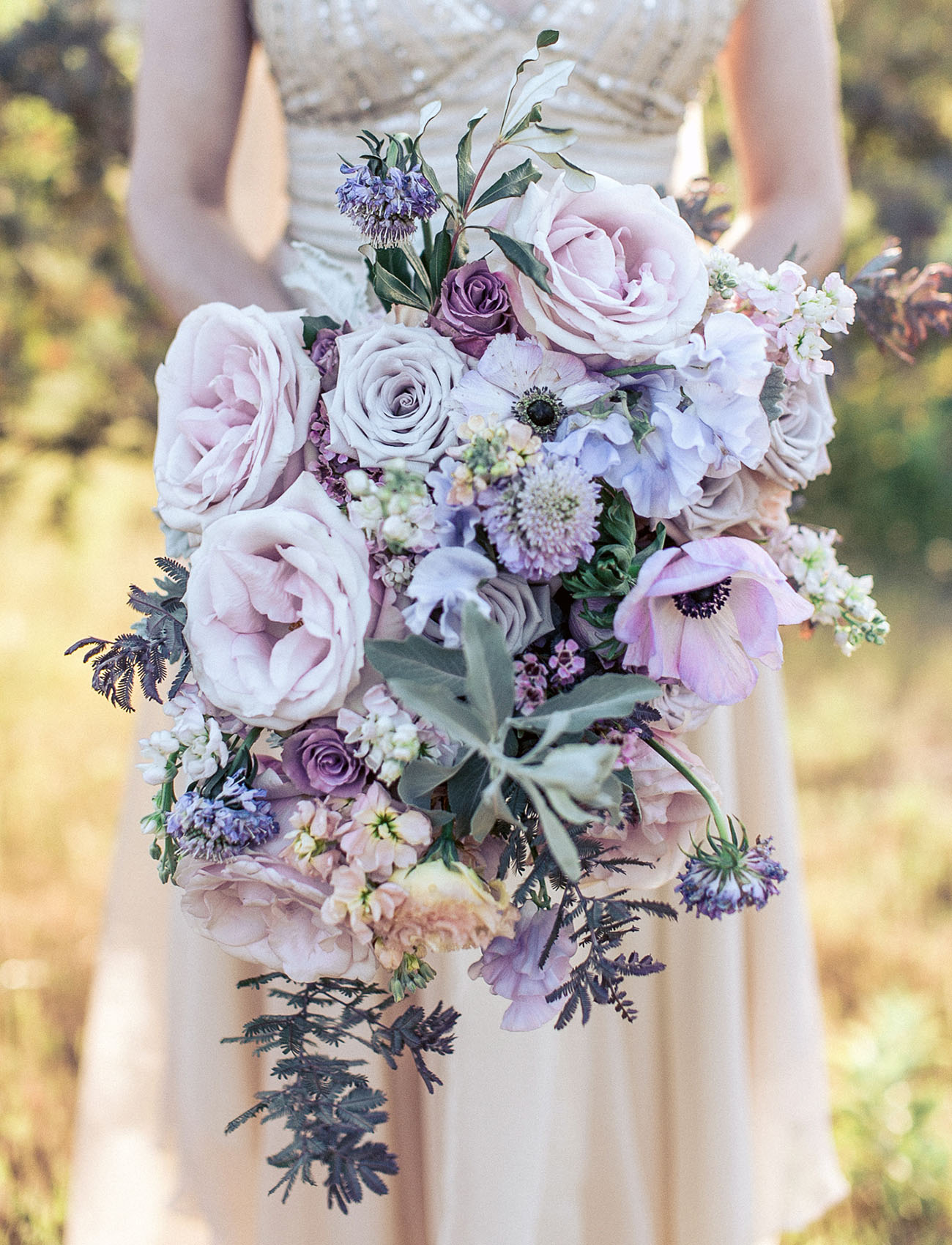 a tender lilac cascading wedding bouquet with lots of various blooms and some pale greenery for a spring bride