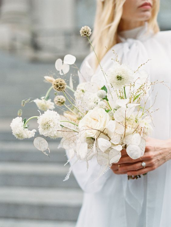 a white wedding bouquet in modern style, with trendy lunaria and some catchy detailing is a fresh idea
