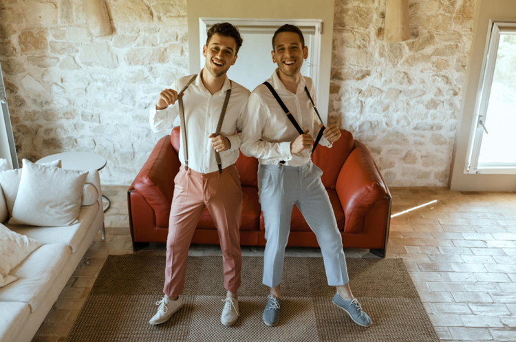One groom chose a terra cotta suit and white sneakers, and the second preferred a dove grey suit with matching sneakers