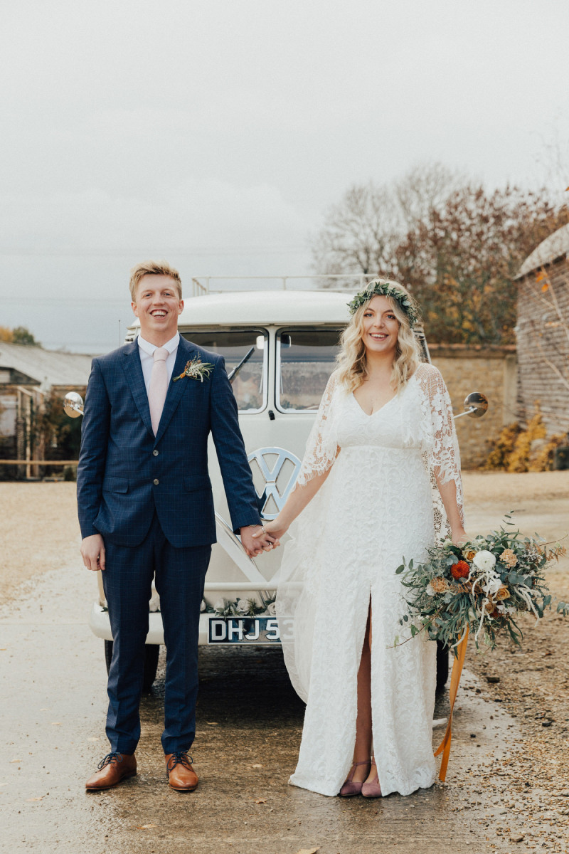 The bride was wearign an A line boho lace wedding dress with a front slit and a greenery crown, the groom was wearing a navy suit with a blush tie