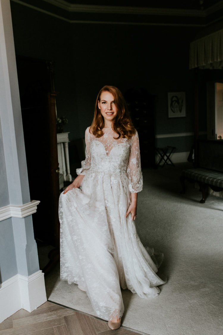 The bride was wearing a beautiful and romantic embellished A-line wedding dress with balloon sleeves and an illusion neckline