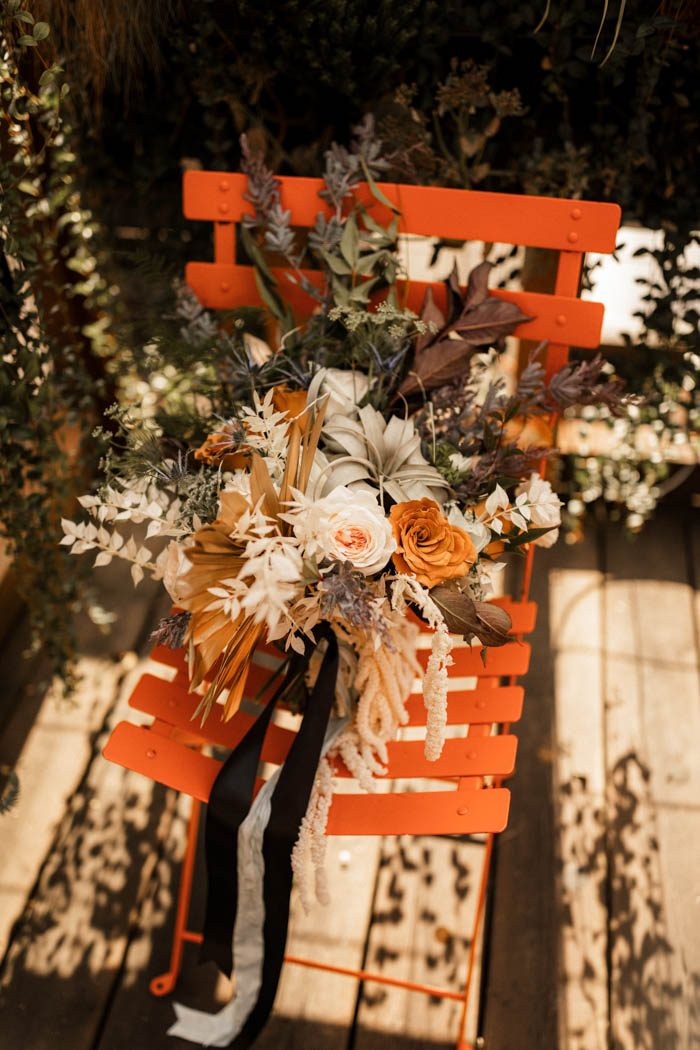 The wedding bouquet was done with rust-colored and blush blooms, greenery and air plants