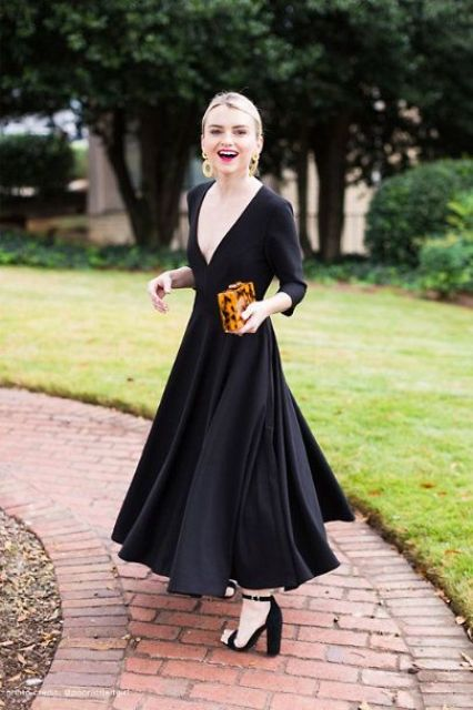 a black maxi dress with a pleated skirt, a plunging neckline and long sleeves, block heels and an animal print clutch, which is a trend