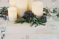 02 a modern winter wedding centerpiece of pillar candles, greenery and privet berries is a stylish and chic idea