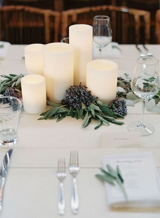 a modern winter wedding centerpiece of pillar candles, greenery and privet berries is a stylish and chic idea