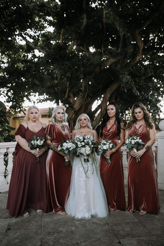 beautifully colored rust to pink mismatching bridesmaid dresses with various necklines and looks
