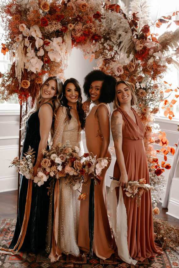 The bridesmaids were wearing mismatching maxi dresses in various colors and of various fabrics
