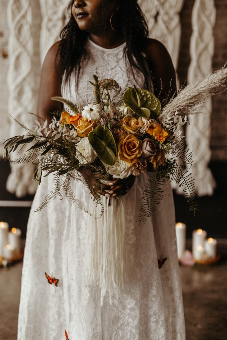 Her wedding bouquet was a moody one, with orange and rust blooms, foliage and pampas grass