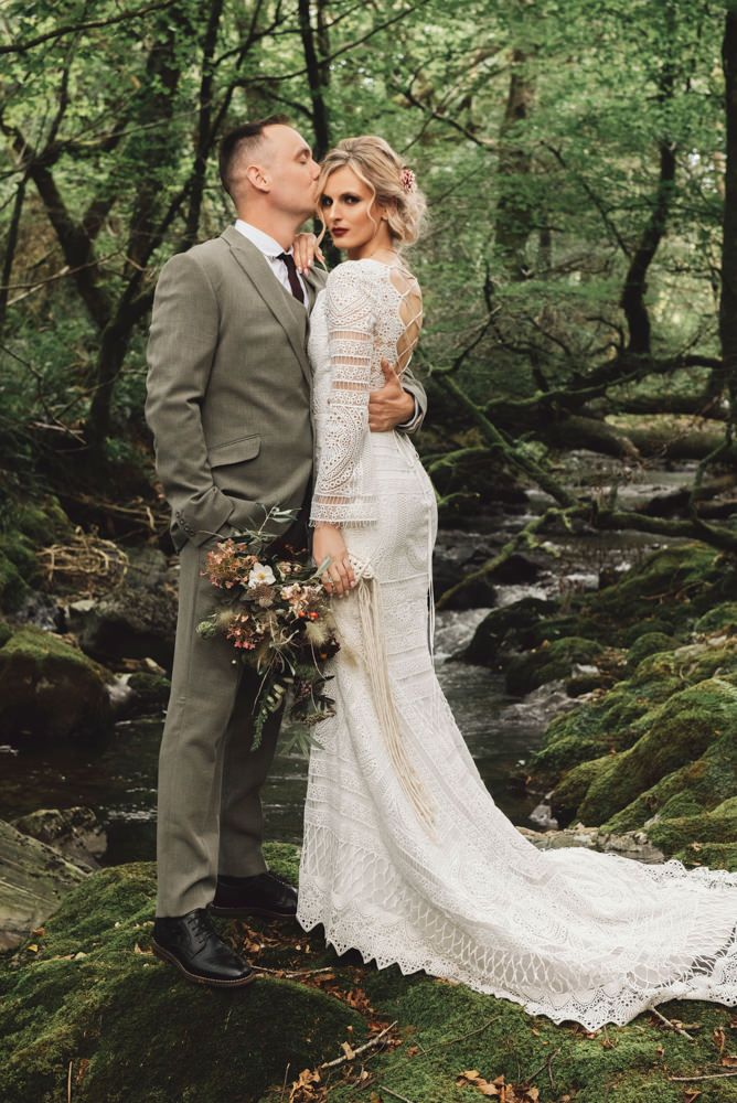 The bride was rocking a boho lace fitting wedding dress with long sleeves and a lace up back