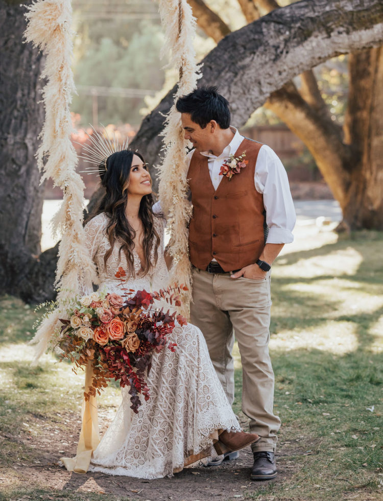 The groom was wearing neutral pants, a brown waistcoat, a white shirt and brown shoes