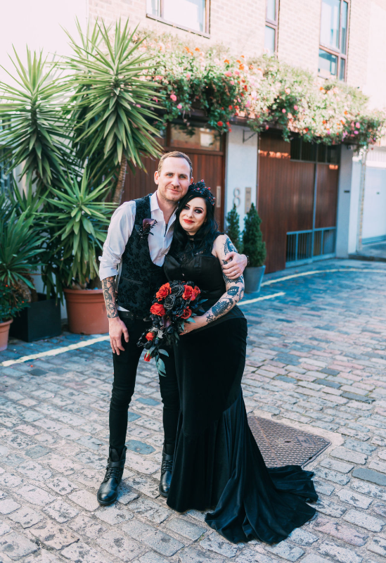 The groom was wearing black skinny jeans, a white shrt, a black floral print waistcoat and black boots