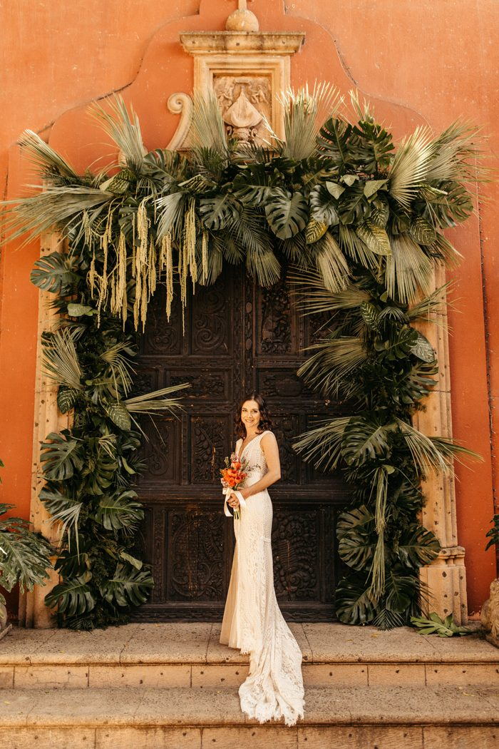 The wedding arch was done with lush tropical greenery to embrace the location
