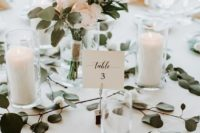 04 pillar candles in glasses, a blush and greenery wedding centerpiece in a vase make up a modern wedding tablescape