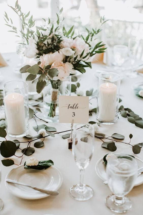 pillar candles in glasses, a blush and greenery wedding centerpiece in a vase make up a modern wedding tablescape