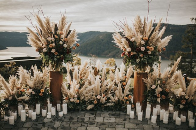 The ceremony space was done with moody blooms, pampas grass and textural greneery plus lots of candles