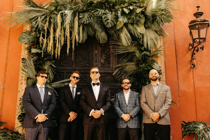 The groom was wearing a black tux and the groomsmen were rocking mismatching suits and looks