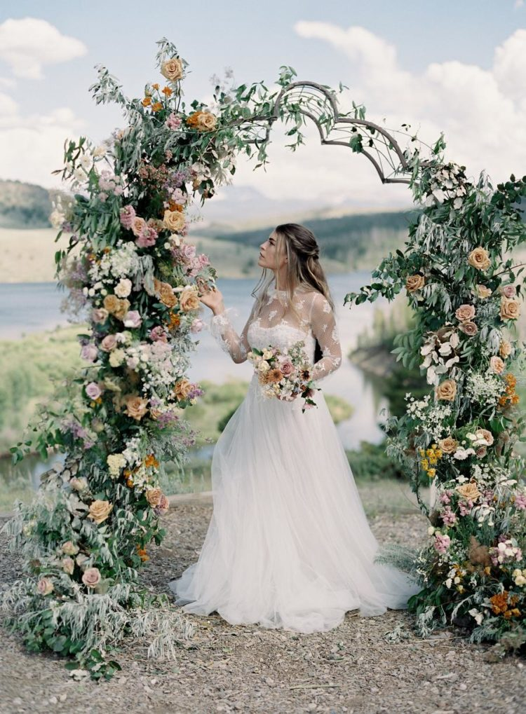The second wedding dress was with an illusion neckline and illusion sleeves, and the wedding arch was done with lush blooms