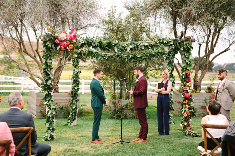 The wedding ceremony space was done with a lush greenery arch that was decorated with bright florals on one corner