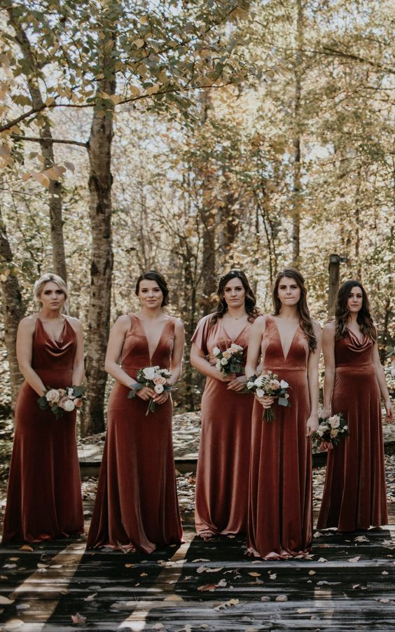chic mismatching rust colored velvet bridesmaid dresses with deep necklines will fit both a fall and a winter wedding