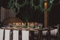 05 greenery wreaths suspended over the table and a matching greenery runner on the table for a chic and natural look