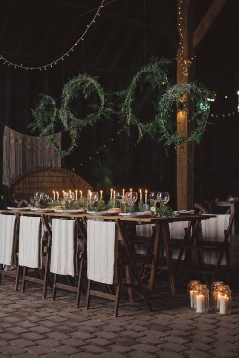 greenery wreaths suspended over the table and a matching greenery runner on the table for a chic and natural look