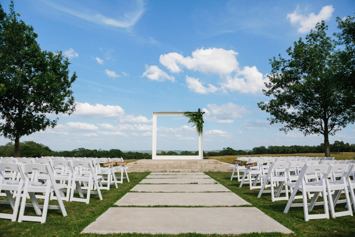 The ceremony space was done minimalist, with white chairs, an oversized frame with fronds on one corner