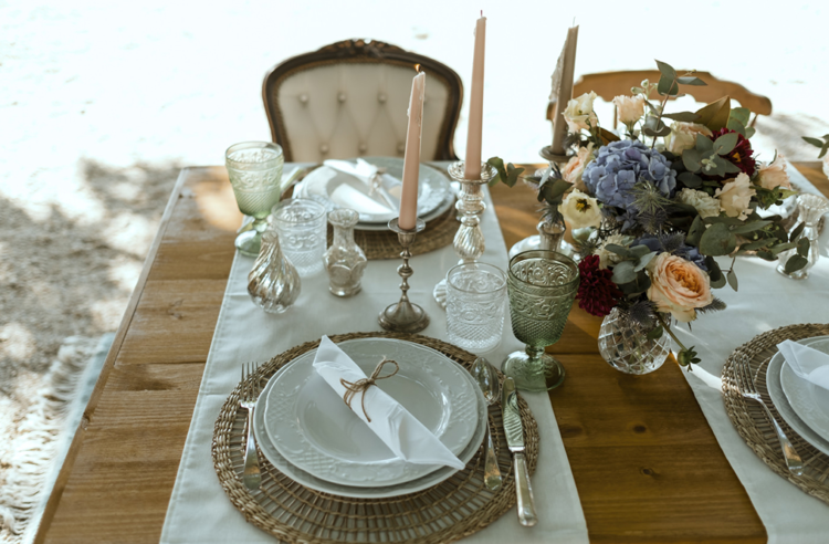 The table was done with woven placemats, elegant metallic candleholders and chic glasses