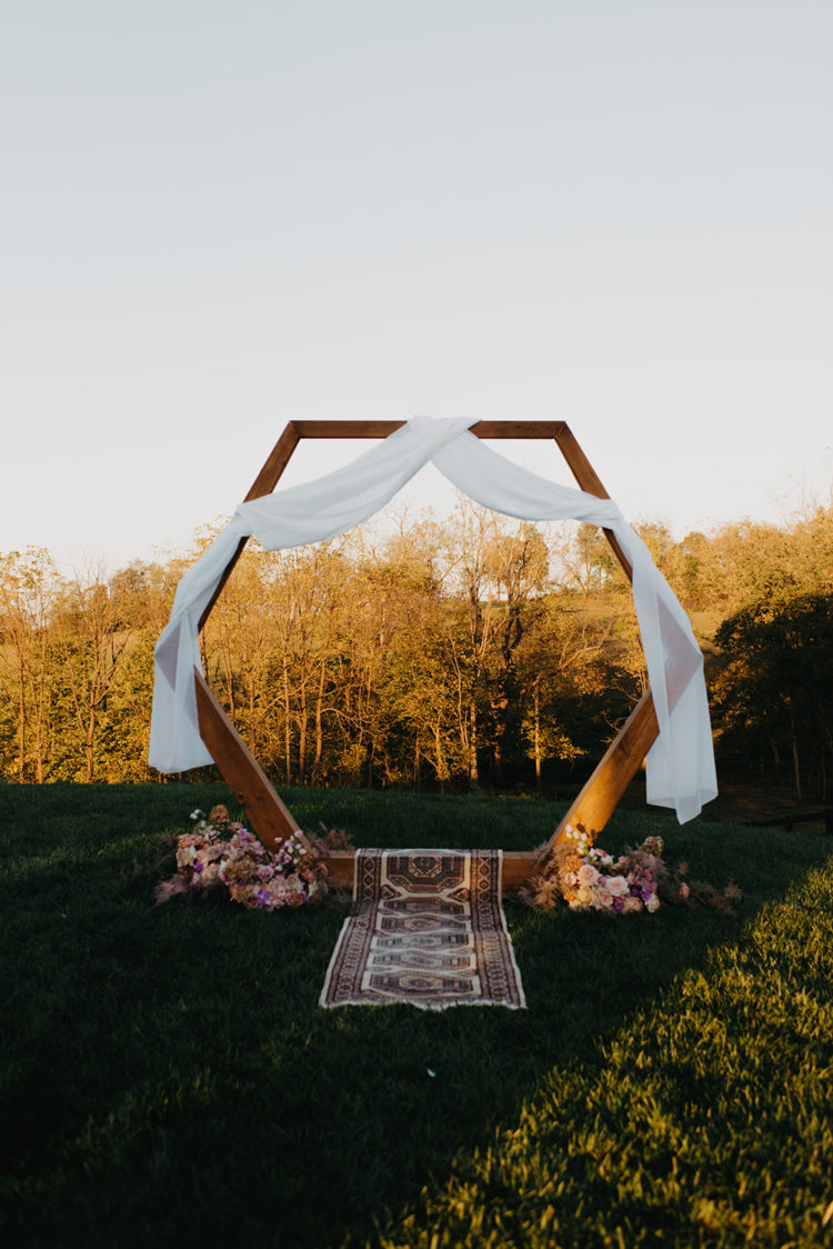 The wedding arch was done with white fabric, lush blooms and a boho rug