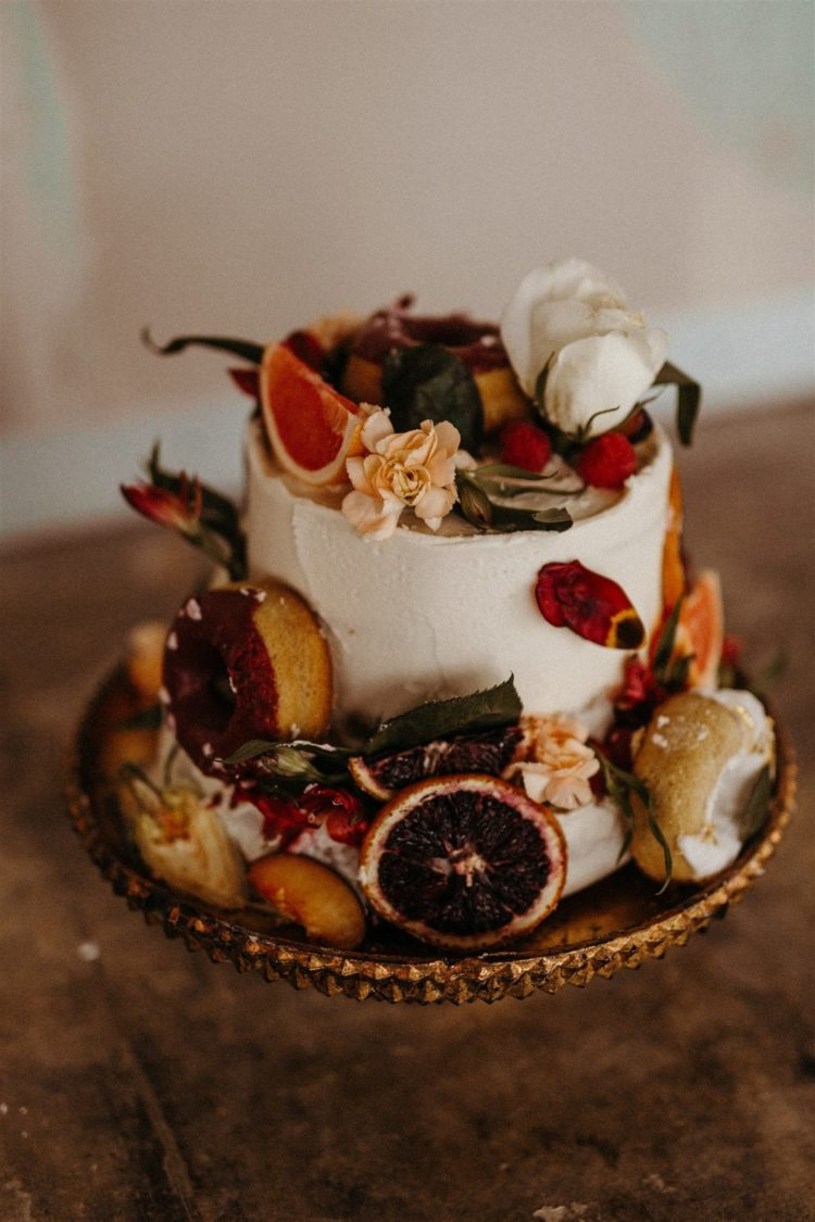 The wedding cake was a white textural one, with fruit fruits, blooms, greenery and foliage
