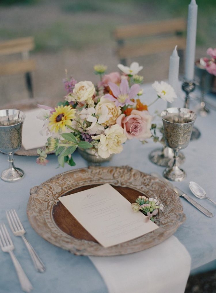 The wedding tablescape was done with a blue tablecloth, the placemats were super refined and a chic floral centerpiece enlivened the table