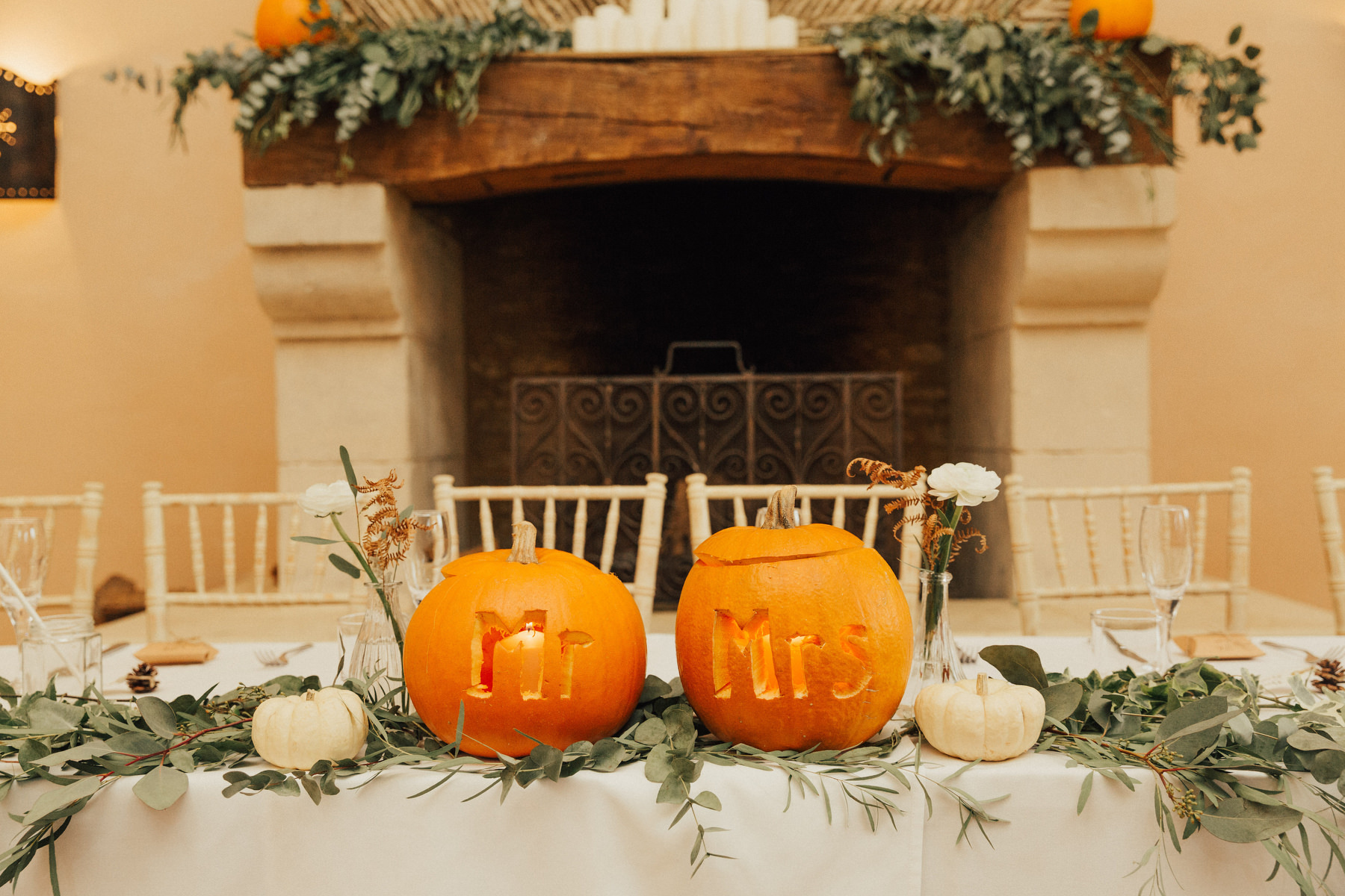 The reception table was decorated with pumpkins in orange and white, carved ones and greenery