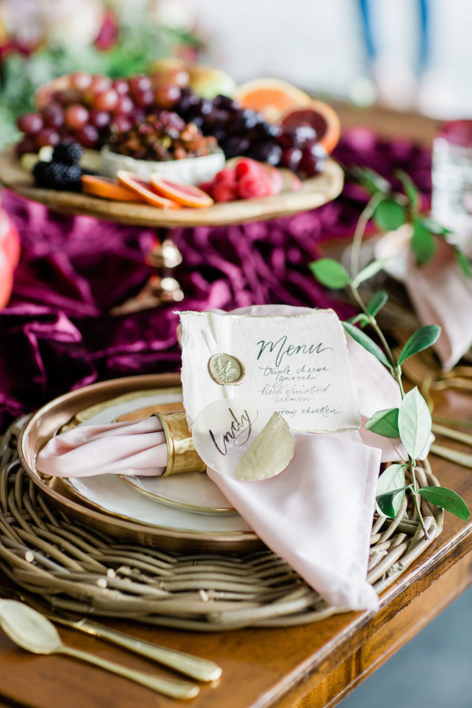 The wedding place setting was done with a woven placemat, metallic plates, blush napkins and a porcelain napkin ring