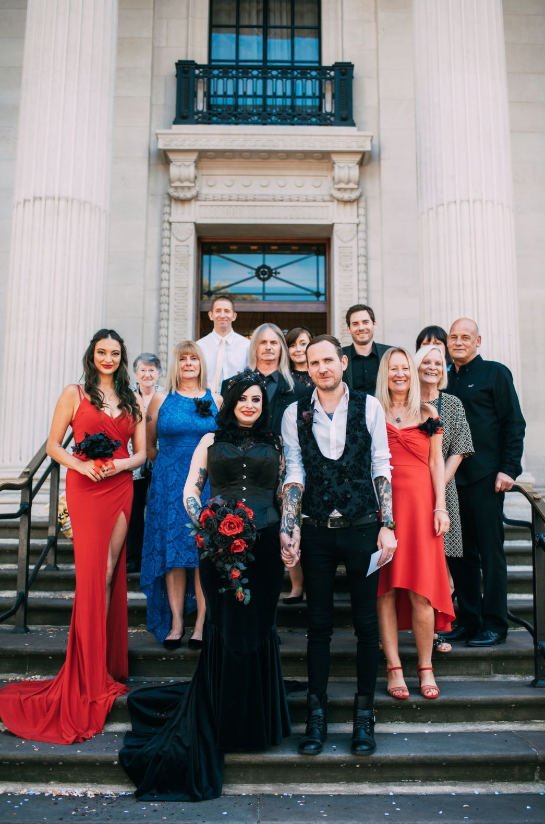 There were only 14 guests present, and the bridesmaids were rocking mismatching red dresses and black bouquets
