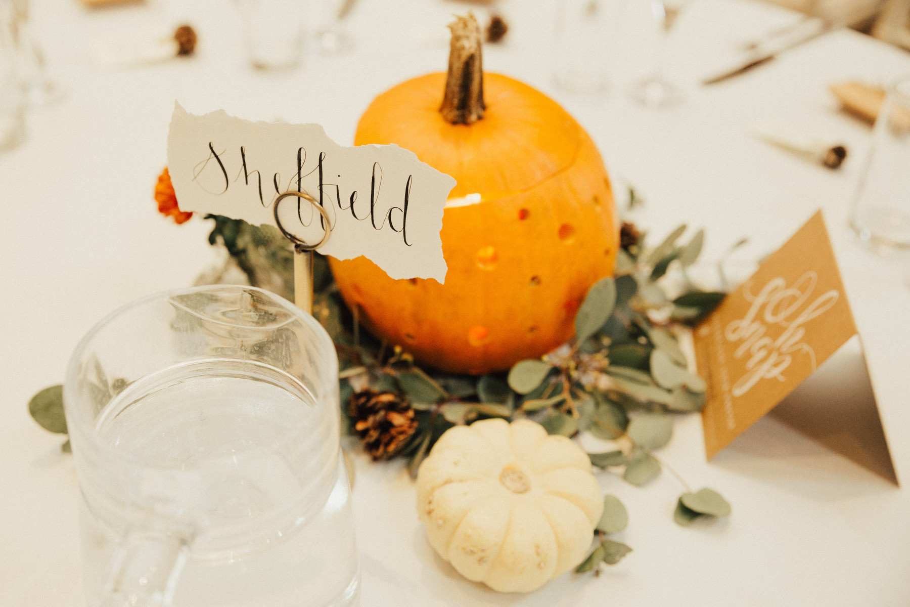 The centerpieces included white and orange pumpkins, greenery and pinecones