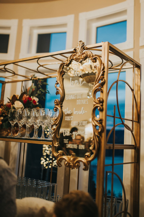 The wedding drink bar was styled with a refined mirror and a refined and chic stand for glasses