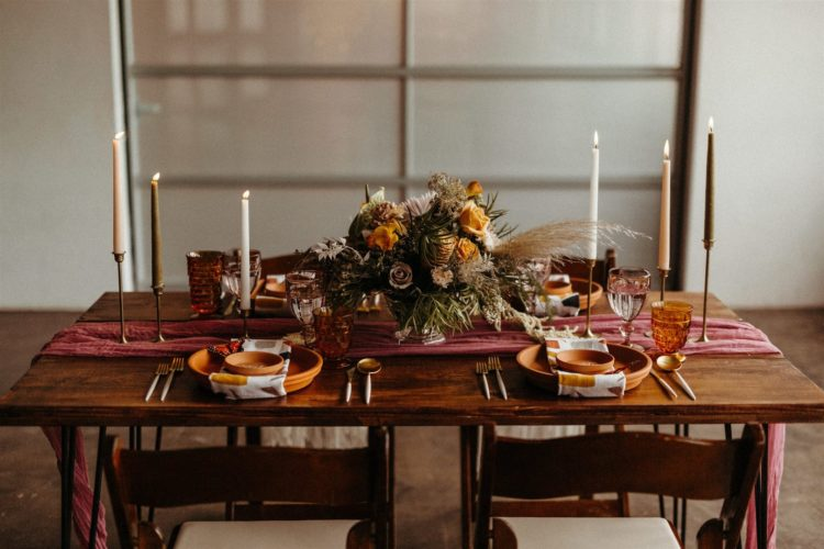The wedding tablescape was done with a pink table runner, tall candles, a bold floral centerpiece and terra cotta plates