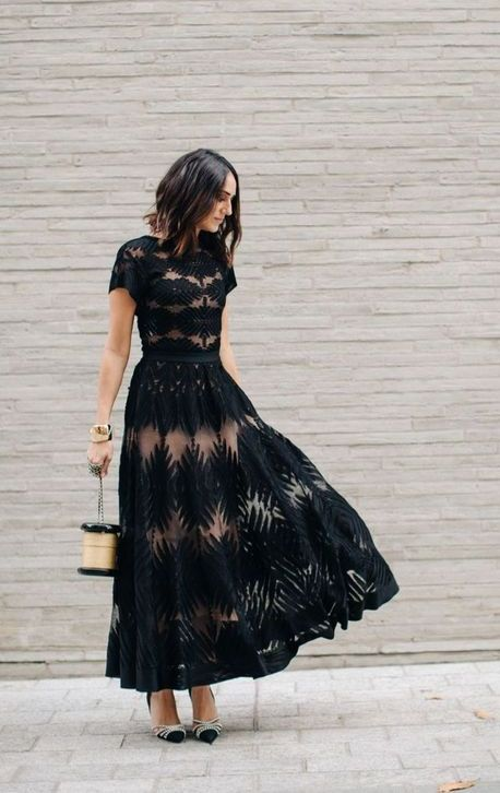 a classy A-line black maxi dress with a high neckline, short sleeves and see-through detailing, embellished shoes and a shiny metallic bag