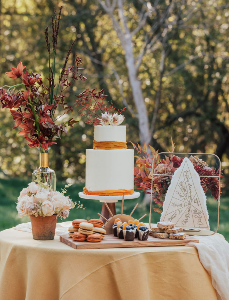 The dessert table was done with sweets, a wedding cake with rust-colored ribbons and bold blooms