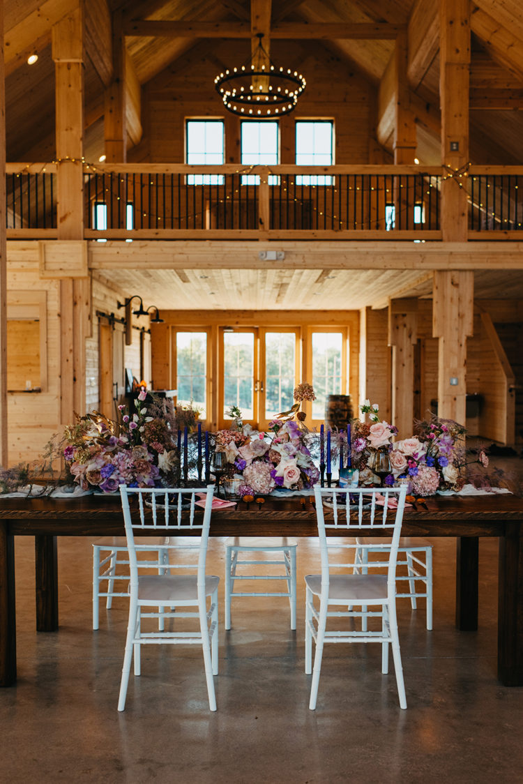 The wedding reception strikes with lush florals at once, and deep colored candles complete the look