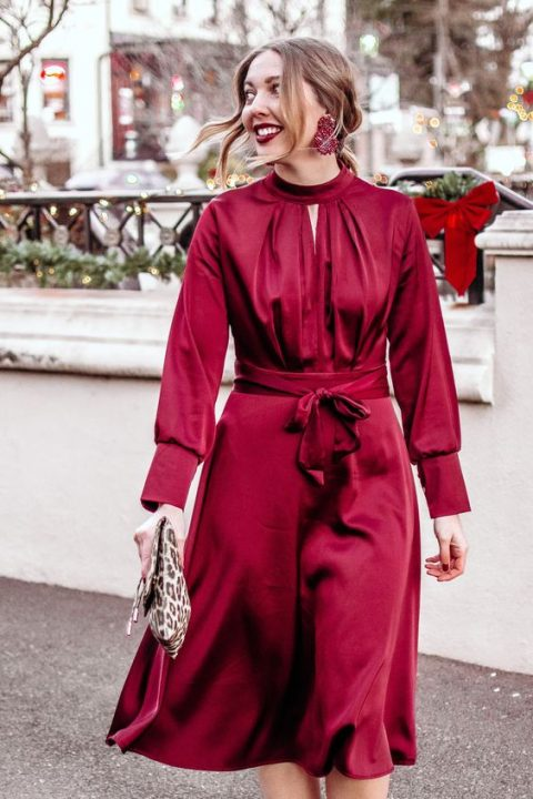 a burgundy knee dress with a high neckline, long sleeves, an animal print clutch and statement earrings