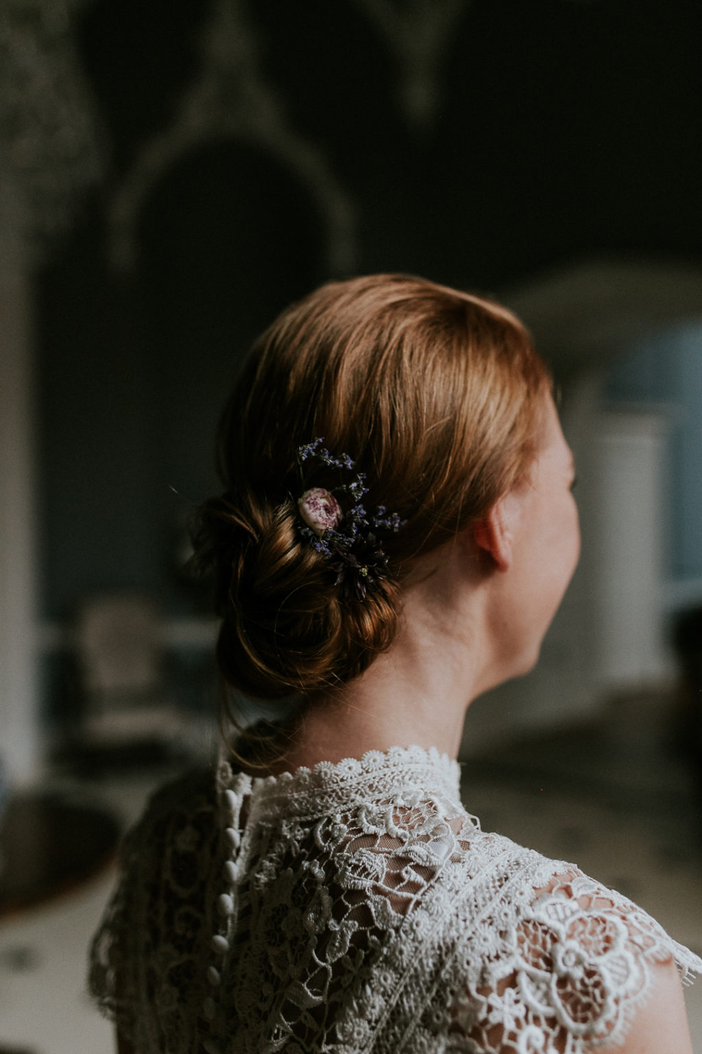 Her red hair was a low updo accented with some dried blooms