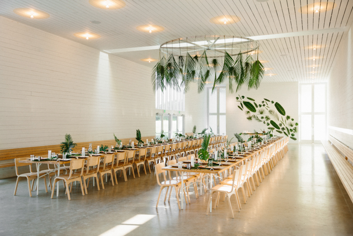 The reception space was done with uncovered tables, fronds and leaves and white porcelain for a minimal feel