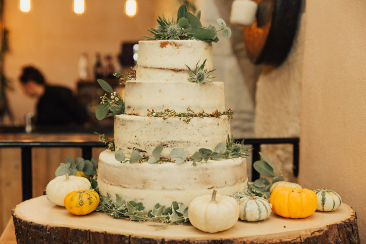 The wedding cake was rustic too, with greenery, berries, thistles and pumpkins around it